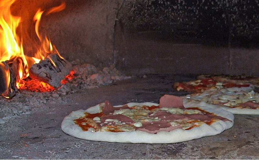 Pizzas bake in a traditional wood-fired brick oven. Photo by Claus Ableiter, Wikipedia Commons.