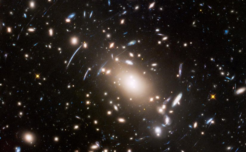 """This view of a massive cluster of galaxies unveils a very cluttered-looking universe filled with galaxies near and far. Some are distorted like a funhouse mirror through a """"space warp"""" phenomenon first predicted by Einstein a century ago. Credit NASA, ESA, and J. Lotz (STScI)"""