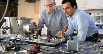 Post-doctoral scholar Peter McMahon, left, and visiting researcher Alireza Marandi examine a prototype of a new type of light-based computer. Credit L.A. Cicero