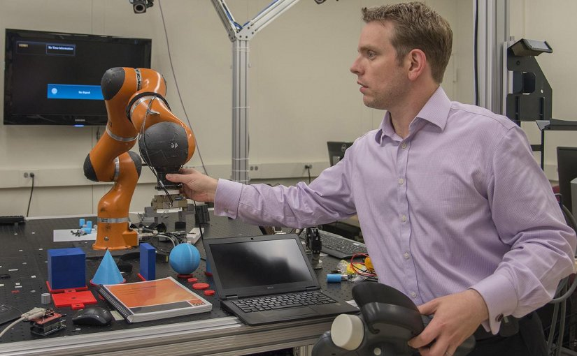 NIST engineer Jeremy Marvel adjusts a robotic arm used to study human-robot interactions. According to a NIST economic study on advanced robotics and automation -- one of four reports on advanced manufacturing -- Marvel's work is the type of research needed to fortify and facilitate this emerging field. Credit Fran Webber/NIST