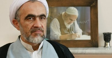 Ahmad Montazeri sits in front of a portrait picture of his late father Hossein Ali Montazeri. Photo via Radio Zamaneh.