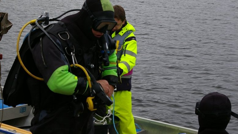 """Divers at the Umeå Marine Sciences Centre prepare for sediment sampling in the sea outside the mesocosm facility. A key aspect, and great challenge, of the project was the necessity to use intact natural """"sediment cores"""" large enough to fit the mesocosm experimental systems. Sediment cores with a diameter of 70 centimeters and a depth of 20 centimeters (and a mass of 70 kilograms) were successfully sampled manually by divers and lifted onboard the research vessel R/S Lotty by crane. Photo: Sofi Jonsson"""