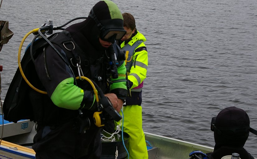 "Divers at the Umeå Marine Sciences Centre prepare for sediment sampling in the sea outside the mesocosm facility. A key aspect, and great challenge, of the project was the necessity to use intact natural ""sediment cores"" large enough to fit the mesocosm experimental systems. Sediment cores with a diameter of 70 centimeters and a depth of 20 centimeters (and a mass of 70 kilograms) were successfully sampled manually by divers and lifted onboard the research vessel R/S Lotty by crane. Photo: Sofi Jonsson"