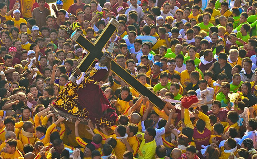 Marshals in yellow lift the Black Nazarene onto its ándas at the start of the Traslación in Manila, Philippines. Photo by Jsinglador, Wikipedia Commons.