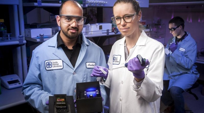 Sandia National Laboratories chemical engineer and lead paper author Aashish Priye offers a view into the Zika box prototype, along with co-authors Sara Bird, a virologist, center, and , a biomedical engineer. Credit Photo by Randy Wong