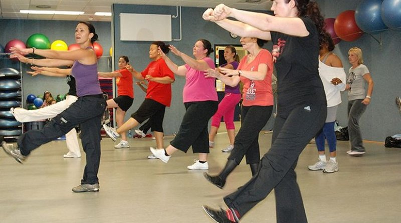 An instructor coaches a Zumba class in a fitness center. Photo by Brittany Carlson (USAG Stuttgart) - United States Army, Wikipedia Commons.