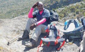 CBK staffer Mr. Gikuhi Ndegwa takes a needed rest on his journey to the summit of Mount Kilimanjaro. Photo Credit: CBK.