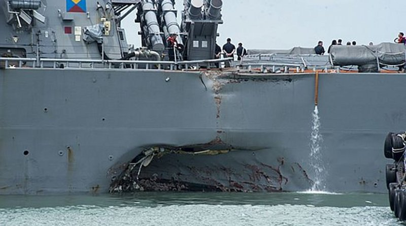 Damage to the portside is visible as the guided-missile destroyer USS John S. McCain (DDG 56) steers towards Changi Naval Base, Republic of Singapore, following a collision with the merchant vessel Alnic MC while underway east of the Straits of Malacca and Singapore. U.S. Navy photo by Mass Communication Specialist 2nd Class Joshua Fulton.