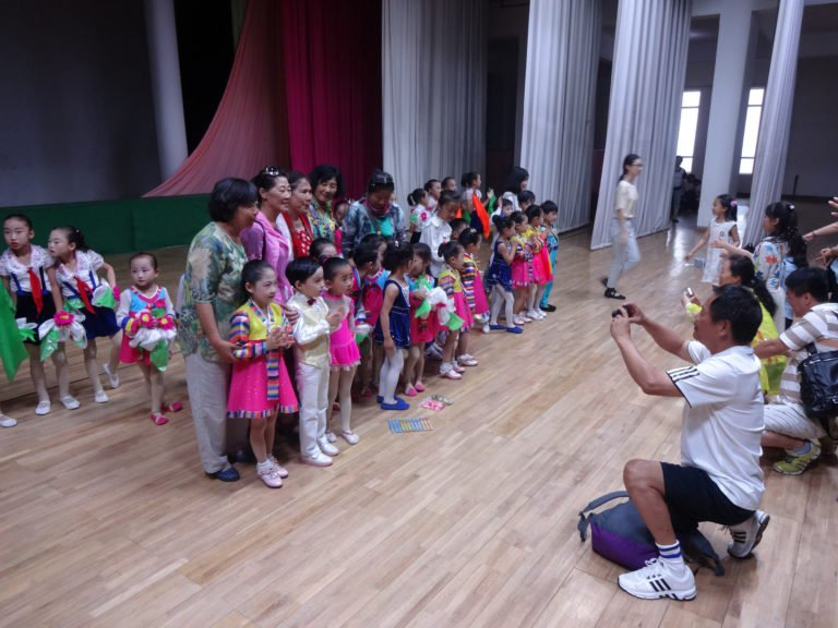 Chinese tourists taking pictures with performers from the children's concert