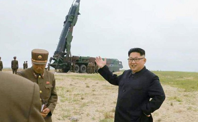 North Korea's Kim Jong Un in front of a missile launcher.