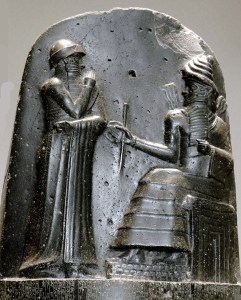 Hammurabi (standing), depicted as receiving his royal insignia from Shamash (or possibly Marduk). Hammurabi holds his hands over his mouth as a sign of prayer[1] (relief on the upper part of the stele of Hammurabi's code of laws). Photo by Mbzt, WIkipedia Commons.