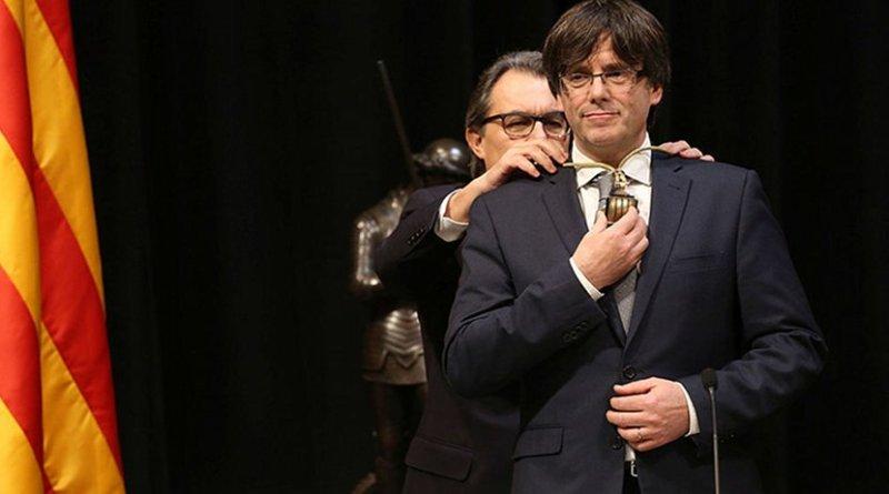 Catalan leader Carles Puigdemont assuming the position of President, in front of his predecessor Artur Mas. Photo Credit: Generalitat de Catalunya, Wikipedia Commons.