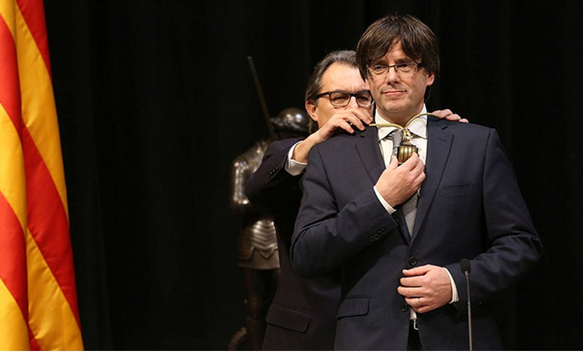 Catalan leader Carles Puigdemont assuming the position of President, in front of his predecessor Artur Mas. Photo Credit: Generalitat de Catalunya, Wikipedia Commons.