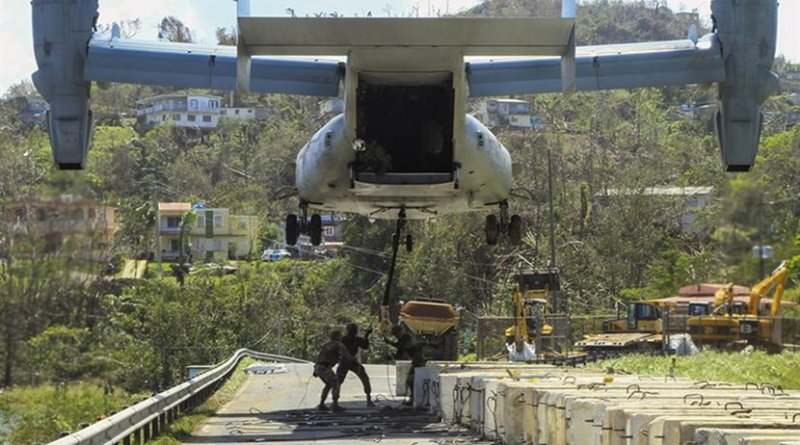 Marines attach a barrier to a V-22 Osprey tilt-rotor aircraft while working to reinforce the Guajataca Dam in Puerto Rico in Hurricane Maria's aftermath, Oct. 3, 2017. Army photo by Pfc. Deomontez Duncan