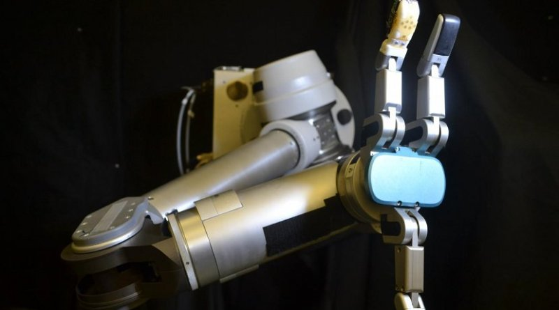 The flexible sensor skin wrapped around the robot finger (orange) is the first to measure shear forces with similar sensitivity as a human hand -- which is critical for successfully gripping and manipulating objects. Credit UCLA Engineering