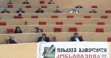 """Lawmakers from the European Georgian displayed a banner in the parliament chamber reading """"Trampled Down Constitution."""" Photo: screenshot."""