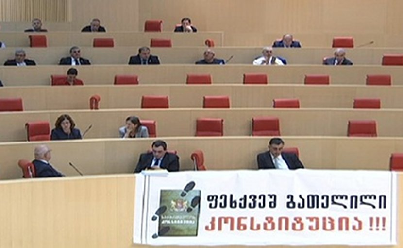 "Lawmakers from the European Georgian displayed a banner in the parliament chamber reading ""Trampled Down Constitution."" Photo: screenshot."