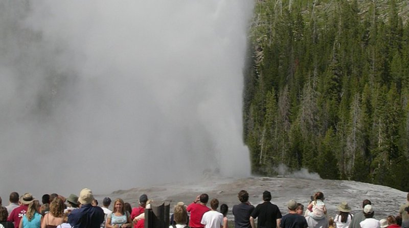 Tourists watch Old Faithful geyser in Yellowstone National Park in Wyoming, United States.