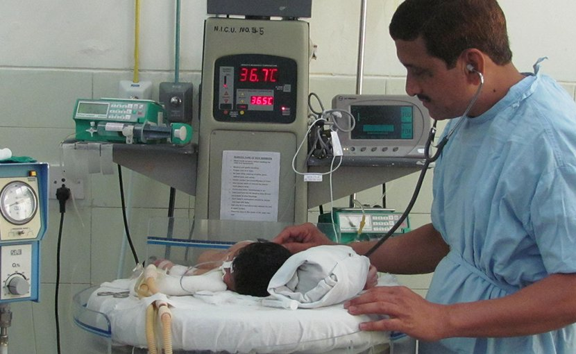 Professor Sangappa Dhaded attending to an infant in the Neonatal Intensive care Unit.