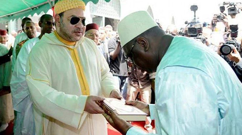 Morocco's King Mohammed VI offering the Holy Koran to the faithful during his June 2015 visit to Africa - religious diplomacy at work.