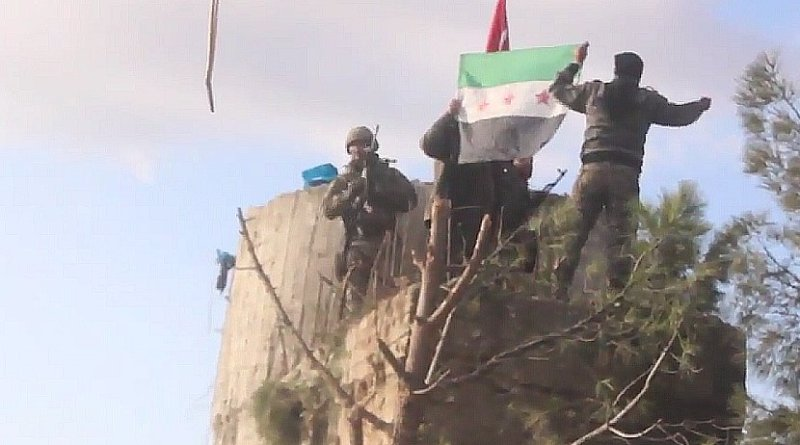 """TFSA fighters on the top of Barsaya mountain, hoisting the Turkish and Syrian indepedence flag while shouting """"Allāhu akbar"""". Photo Credit: Qasioun News Agency, Wikipedia Commons."""