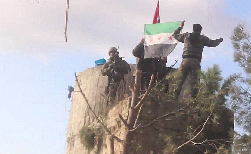 "TFSA fighters on the top of Barsaya mountain, hoisting the Turkish and Syrian indepedence flag while shouting ""Allāhu akbar"". Photo Credit: Qasioun News Agency, Wikipedia Commons."