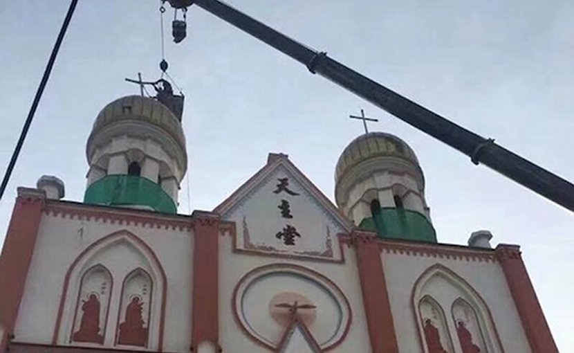 Under orders from communist authorities, workers in a crane get to work on removing religious features from Yining Catholic Church in Urumqi Diocese. (Photo supplied)