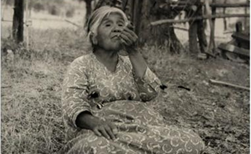 This is a 1945 picture of a Yokuts Native American woman smoking a pipe. Credit Clifford Relander