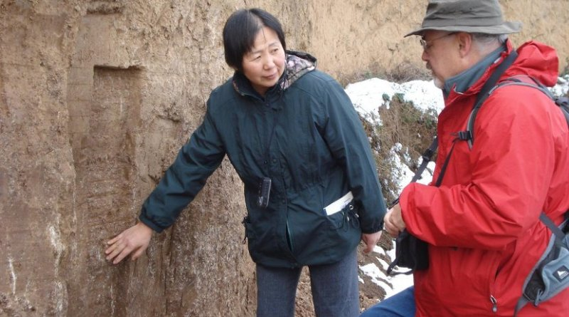 Weijian Zhou (left) of the Institute of Earth Environment, Chinese Academy of Sciences in Xi'an and Warren Beck (right) of the University of Arizona at a cross-section of a hill near Xi'an, China. The layers of loess soil shown in the photo represent thousands of years of soil deposition. Credit © 2009 Xian Feng, Institute of Earth Environment, Chinese Academy of Sciences