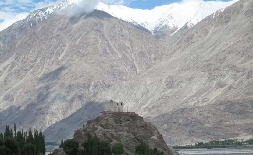 This is a temple in the Nubra Valley of Ladakh, India, which is in the study area. The picture illustrates the enormous size and scale of the mountains in this part of the Himalayas. Credit Wendy Bohon