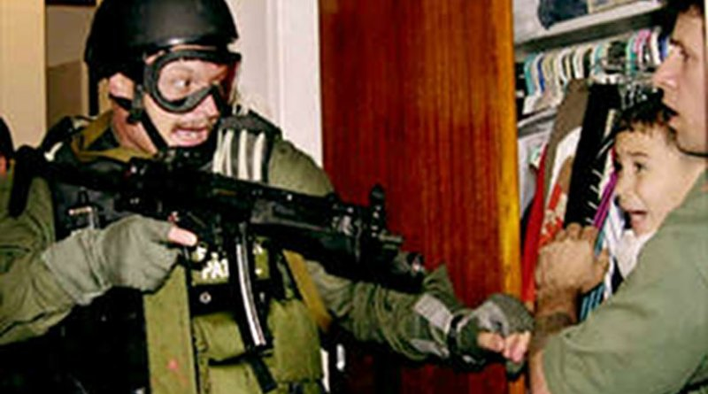 Unidentified border patrol officer during the seizure of Elián González from his uncle's residence on April 22, 2000. Photo Credit: Lowe resolution of photograph taken by Alan Diaz of the Associated Press, Wikimedia Commons.