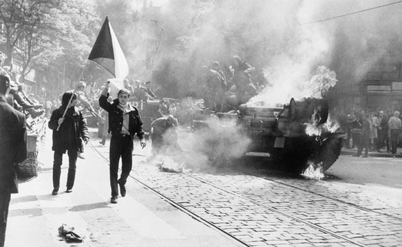 During the Soviet invasion of Czechoslovakia, Czechoslovaks carry their national flag past a burning tank in Prague. Photo Credit: CIA, Wikimedia Commons.