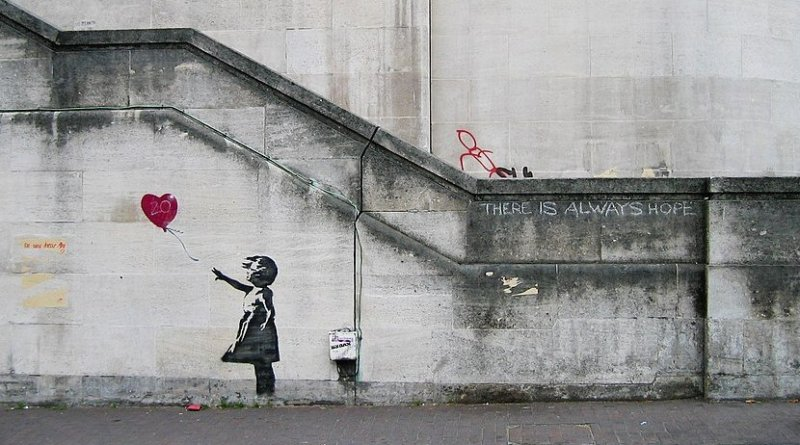 """Original mural of """"Balloon Girl"""" by Banksy on Waterloo Bridge in South Bank in 2004. Photo Credit: Dominic Robinson, Wikipedia Commons."""