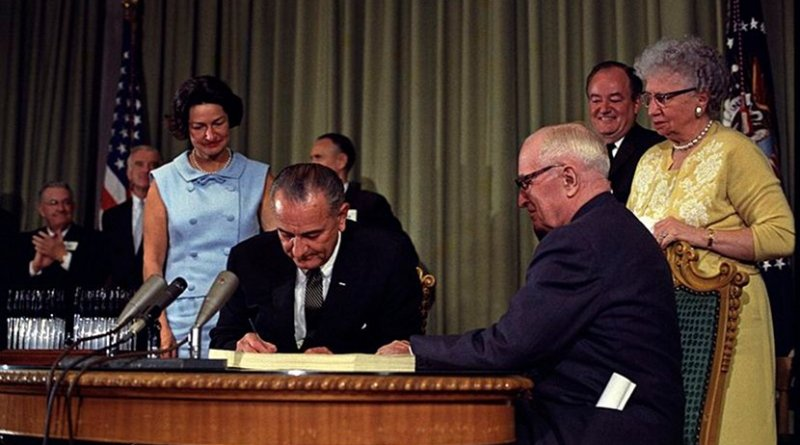 President Lyndon B. Johnson signing the Medicare Bill at the Harry S. Truman Library in Independence, Missouri. Former president Harry S. Truman is seated at the table with President Johnson. The following are in the background (from left to right): Senator Edward V. Long, an unidentified man, Lady Bird Johnson, Senator Mike Mansfield, Vice President Hubert Humphrey, and Bess Truman. Photo Credit: Lyndon Baines Johnson Library (Austin, Texas), Wikimedia Commons.