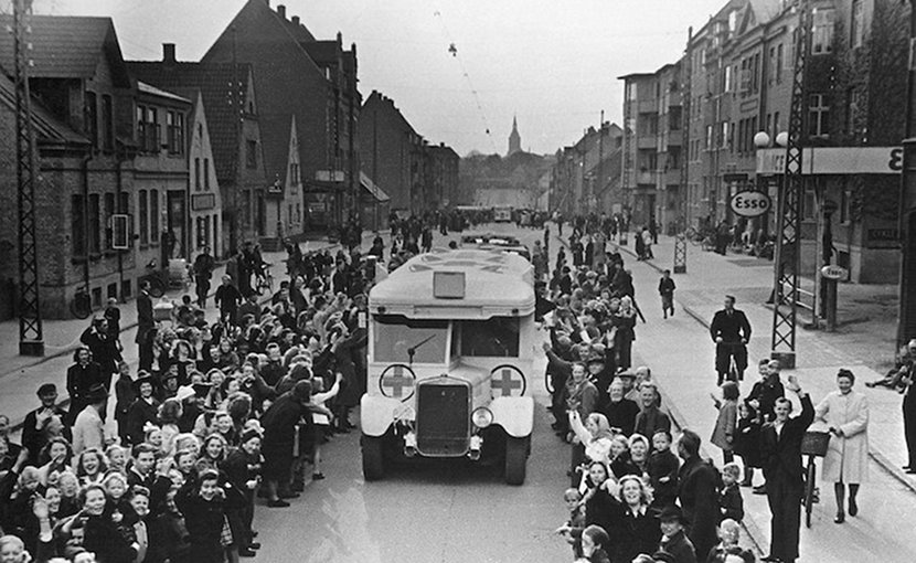 As part of Count Folke Bernadotte action, Danish Red Cross buses drive through Odense on the way to Sweden, carrying Danish prisoners from German concentration camps April 17, 1945. CC BY-SA 2.0.