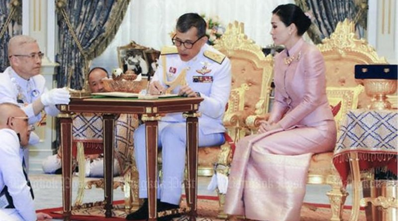 Thailand's King Maha Vajiralongkorn signs marriage registration documents while Queen Suthida looks on. Photo Credit: Thailand Bureau of the Royal Household