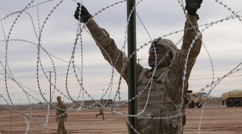 Soldier with 541st Engineer Company, Special Purpose Marine Air-Ground Task Force 7, moves concertina wire over stake on practice barricade at Naval Air Facility El Centro in California. (U.S. Marine Corps/Asia J. Sorenson)