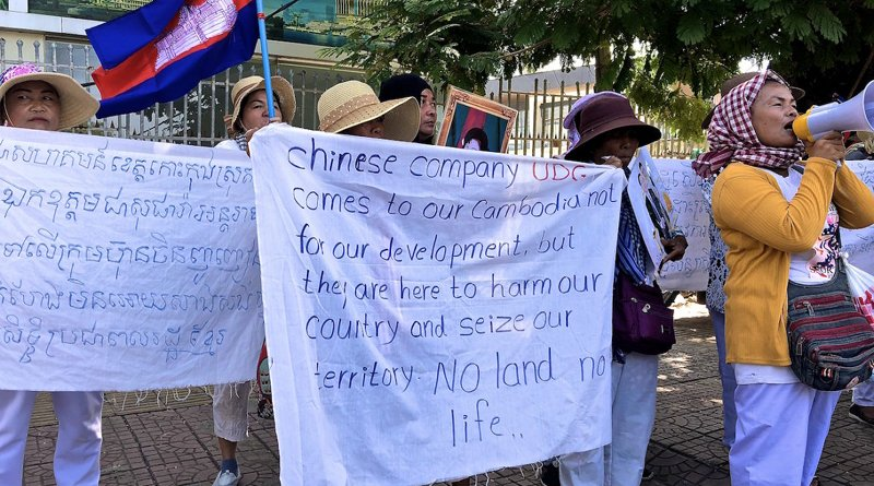 Villagers protesting UDG outside the Chinese Embassy hold up signs and chant into a megaphone. Photo by Andrew Nachemson.