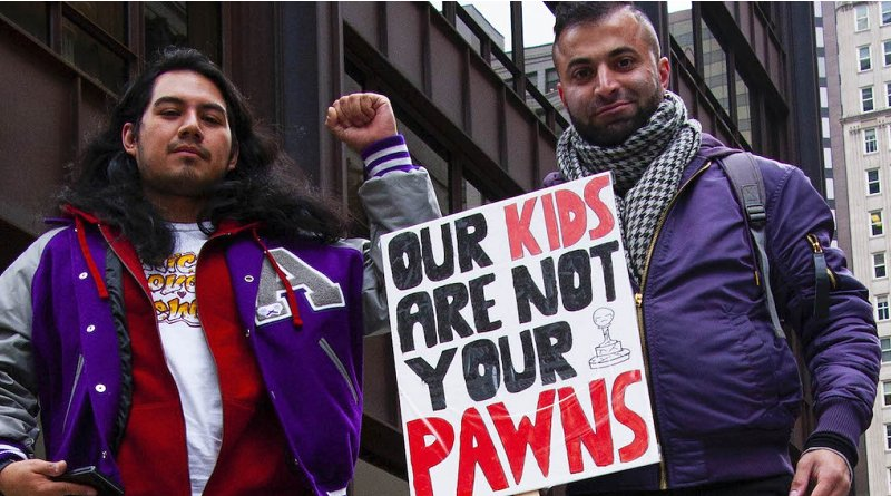 """Two striking Chicago teachers hold a sign stating, """"Our kids are not your pawns."""" Photo credit: Charles Edward Miller. This image has been cropped and modified for size. CC BY-SA 2.0."""