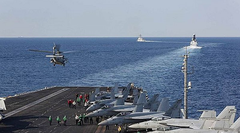 The aircraft carrier USS Abraham Lincoln (CVN 72) transits the Strait of Hormuz as an MH-60S Sea Hawk helicopter from the Nightdippers of Helicopter Sea Combat Squadron (HSC) 5 lifts off from the flight deck. (U.S. Navy photo by Mass Communication Specialist Seaman Stephanie Contreras/Released)