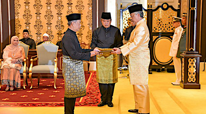 Incoming Malaysian Prime Minister Muhyiddin Yassin (left) receives documents from King Al-Sultan Abdullah Ri'ayatuddin Al-Mustafa Billah before taking the oath of office at the National Palace in Kuala Lumpur, March 1, 2020. Courtesy Malaysia Information Department