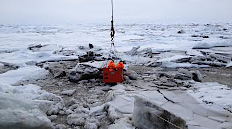 This image shows sediment-rich sea ice in the Transpolar Drift Stream. A crane lowers two researchers from the decks of the icebreaker RV Polarstern to the surface of the ice to collect samples. CREDIT Photo Credit: R. Stein, Alfred Wegener Institute