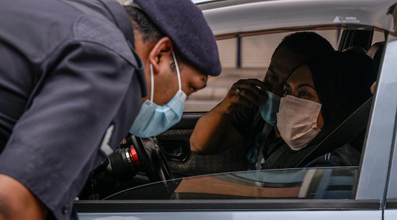 A Malaysian police officer questions a driver at a coronavirus roadblock in Kuala Lumpur, March 19, 2020.S. Mahfuz/BenarNews