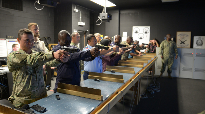 Foreign students try out a firearms training simulator at the Center for Surface Combat Systems Unit, Naval Station Great Lakes, Ill., Sept. 10, 2019. Photo Credit: Brian Walsh, Navy