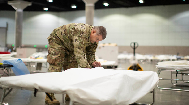 An airman with the California Air National Guard sets up a hospital bed in a medical station inside the Los Angeles Convention Center, March 29, 2020. Photo Credit: Air Force Staff Sgt. Crystal Housman