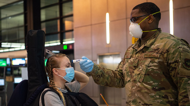 Air Force Senior Airman Kevin Gray II, a passenger service specialist with the 62nd Aerial Port Squadron, takes the temperature of a passenger traveling to Asia at the Seattle-Tacoma International Airport in Seattle, April 30, 2020. Passengers with a fever of 100.4 degrees or higher are denied travel as a precaution against the spread of COVID-19. Photo Credit: Air Force Senior Airman Tryphena Mayhugh