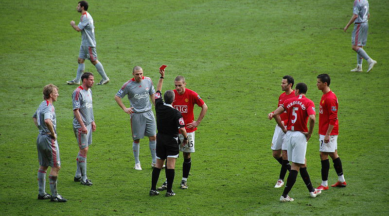 Referee Alan Wiley shows Nemanja Vidic of ManUtd the Red Card during the Premier League match at Old Trafford (Manchester) between Manchester United FC and Liverpool FC on March 14, 2009. Photo Credit: Sdo216, Wikimedia Commons