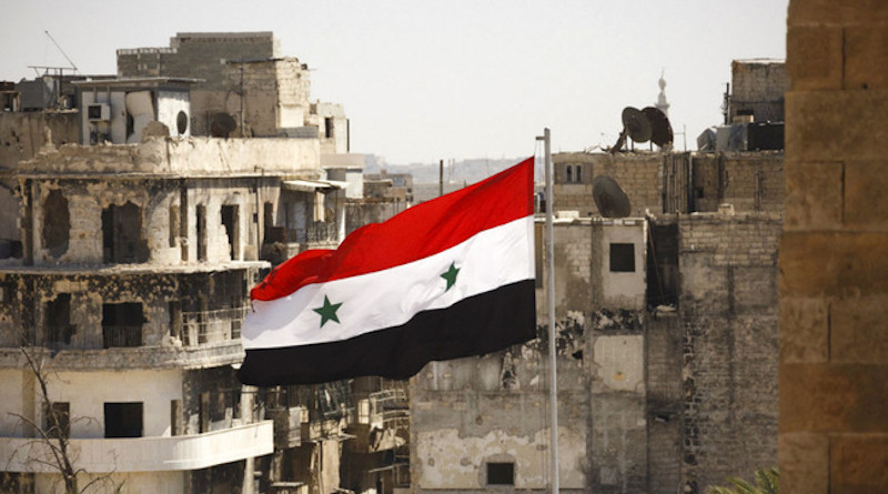 Syria's flag flies in bombed city. Photo Credit: Mil.ru