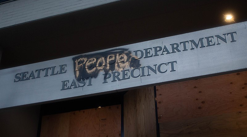 """The entrance sign Seattle East Precinct in the Capitol Hill Autonomous Zone in Seattle, WA on June 9, 2020. The word """"police"""" is covered up with """"People's"""". Photo Credit: Swoggle, Wikipedia Commons"""