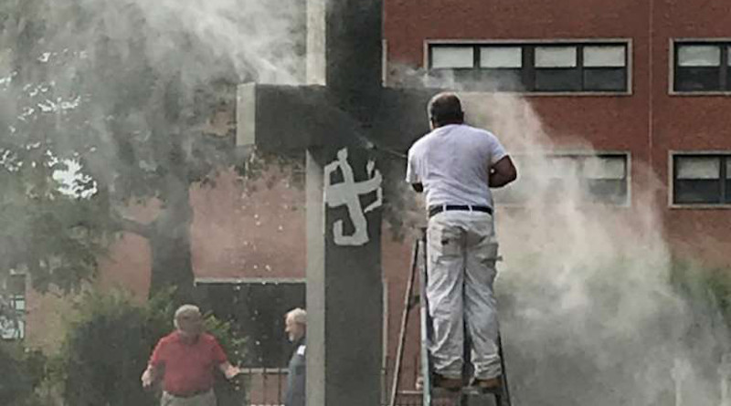 Paint is removed from the central cross at the campus cemetery, Providence College, June 22. Image courtesy of NBC10/ WJAR
